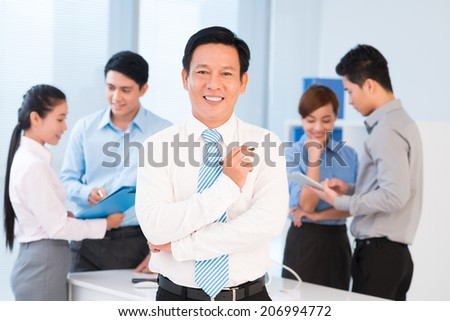 Portrait of confident team leader and managers working in the background