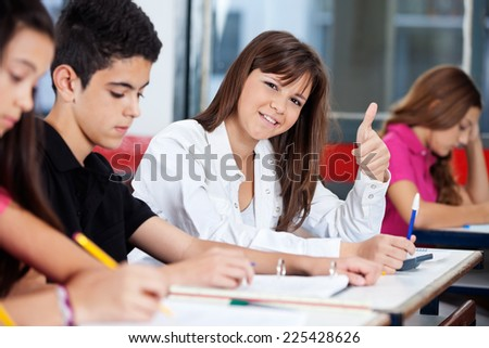 Portrait of confident teenage girl gesturing thumbs up while friends studying in classroom