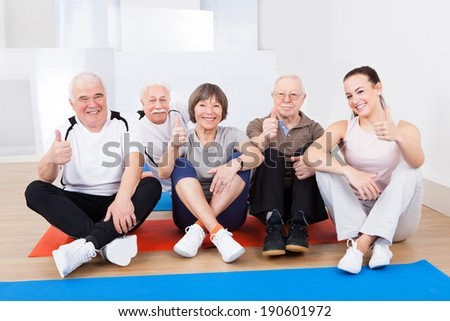 Portrait of confident trainer with senior customers sitting on floor at gym