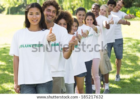 Portrait of confident volunteers gesturing thumbs up while standing in a line at park
