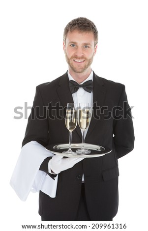 Portrait of confident waiter carrying champagne flutes on tray over white background