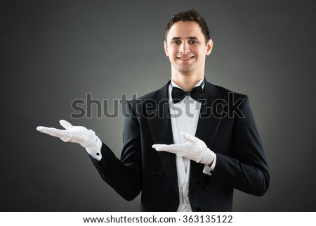 Portrait of confident waiter presenting invisible product against gray background - stock photo