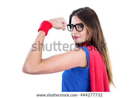 Portrait of confident woman in superhero costume while flexing muscles on white background - stock photo