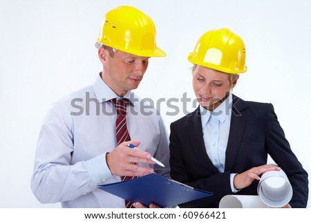 Portrait of confident worker discussing a project with his pretty colleague near by - stock photo