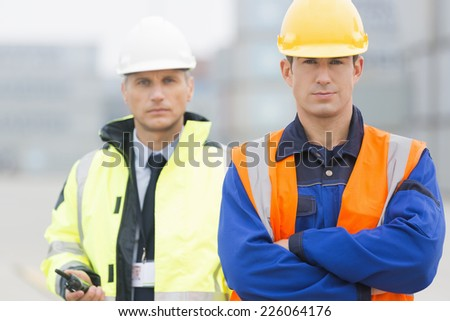 Portrait of confident worker standing with coworker in shipping yard - stock photo