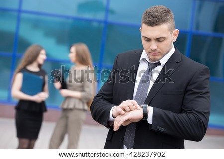 Portrait of confident young business man looking at watch with serious facial expression outdoors. Successful attractive  caucasian man on the street in summer with businesspeople on the background - stock photo