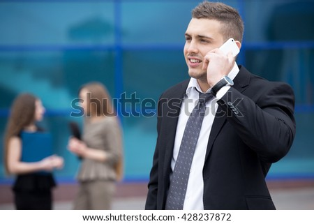 Portrait of confident young business man looking sideways while talking on smartphone outdoor. Successful attractive man using mobile phone, making call on the street. Businesspeople on the background - stock photo