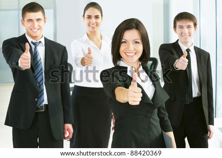 Portrait of confident young business people with thumbs up sign - stock photo