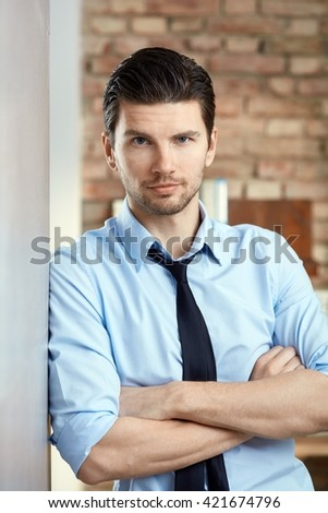 Portrait of confident young businessman looking at camera. - stock photo