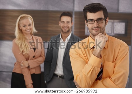 Portrait of confident young businessman looking at camera, colleagues standing at background. - stock photo