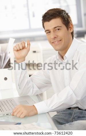 Portrait of confident young businessman sitting in office with laptop computer, smiling at camera.?
