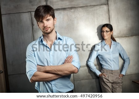 Portrait of confident young businessman standing arms crossed, businesswoman standing behind.