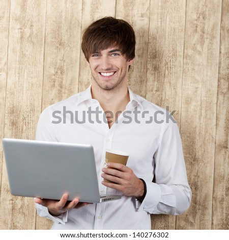 Portrait of confident young businessman with disposable cup and laptop standing against wooden wall - stock photo