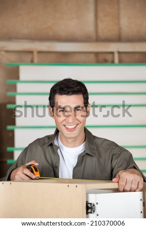 Portrait of confident young carpenter measuring cabinet with tape in workshop