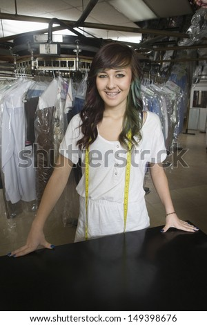 Portrait of confident young laundry owner standing at counter