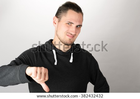 Portrait of confident young man looking at camera and showing his thumbs down while standing against grey background - stock photo