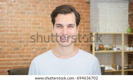 Portrait of confident young man smiling and  standing in his office