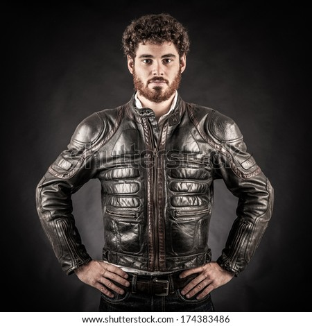 Portrait of confident young man wearing leather jacket against black background.  - stock photo