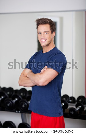 Portrait of confident young man with arms crossed standing in gym - stock photo
