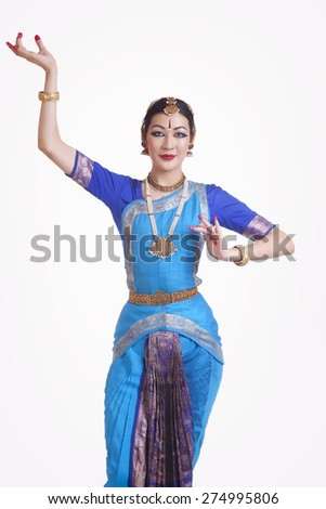 Portrait of confident young woman performing Bharatanatyam over white background - stock photo