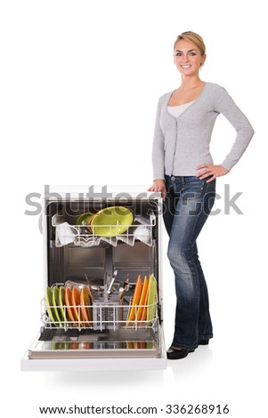 Portrait of confident young woman standing arms crossed while leaning on dishwasher over white background - stock photo