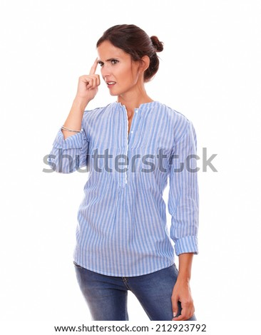 Portrait of confused adult brunette on blue blouse wondering and looking to her right while standing on isolated white background - copyspace - stock photo