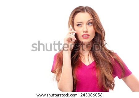 Portrait of confused young lady on purple t-shirt talking on her phone while looking to her right and standing on isolated white background - copyspace - stock photo