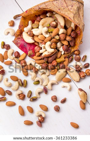 portrait of container from leaves with almonds and mix berries spilling out on white table - stock photo
