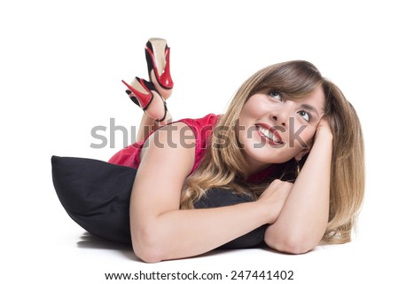 Portrait Of Contemplated Smiling Woman With Pillow Lying On Floor - stock photo