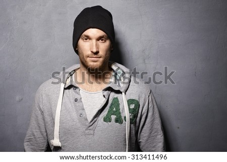 Portrait of contemporary young man standing against grey wall, looking at camera. - stock photo