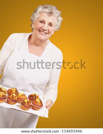 portrait of cook senior woman holding a chocolate muffins tray over orange background - stock photo