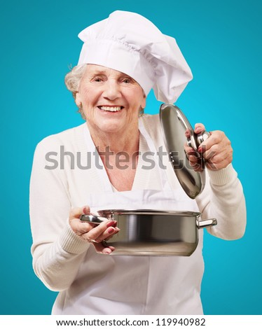portrait of cook senior woman opening sauce pan over blue - stock photo