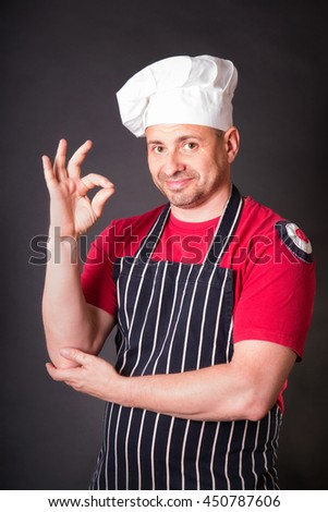 Portrait of cook with gesture okay in the studio on a black background - stock photo