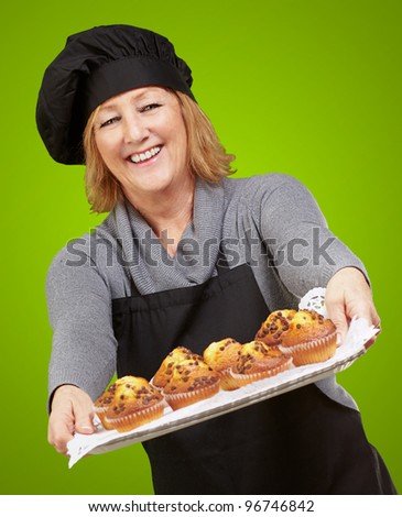portrait of cook woman showing a homemade muffins tray over green background - stock photo