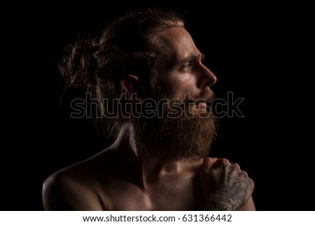 Portrait of cool tattooed bearded hipster guy on black background in studio photo. Expression and fashion