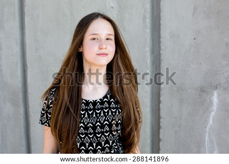 portrait of cool young and beautiful caucasian blonde teenager hipster girl with long gorgeous hair is posing smiling and having fun - stock photo