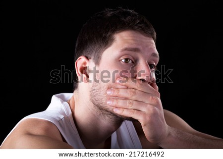 Portrait of coughing man on black background