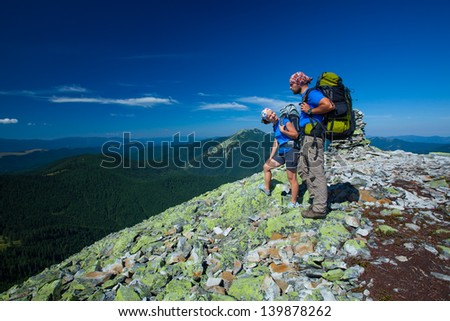 Portrait of couple at the top of the mountain - stock photo