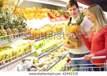 Portrait of couple choosing fruits in supermarket - stock photo