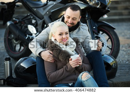 Portrait of couple drinking coffee and chatting near motorcycle - stock photo