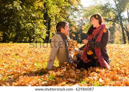Portrait of couple enjoying golden autumn fall season - stock photo