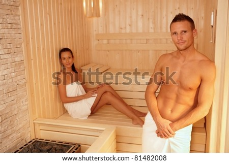 Portrait of couple in sauna on wellness weekend, smiling at camera.? - stock photo