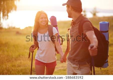 Portrait of couple of happy hikers walking in the countryside - stock photo