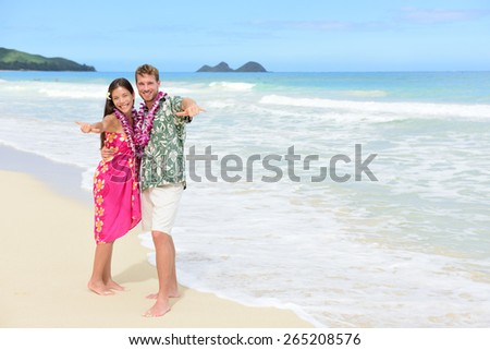 Portrait of couple of tourists happy standing on Hawaiian beach at their Hawaii vacation. Asian woman and Caucasian man wearing flower lei garland and Aloha clothing showing Shaka hand sign on travel. - stock photo