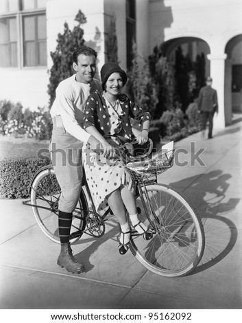 Portrait of couple on bicycle together - stock photo