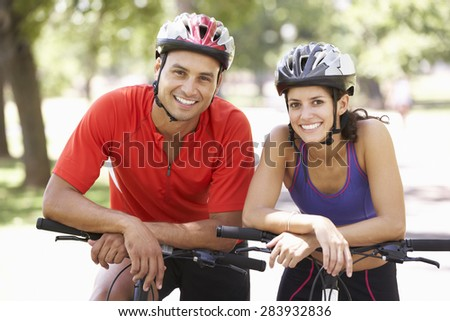Portrait Of Couple On Cycle Ride Through Park - stock photo