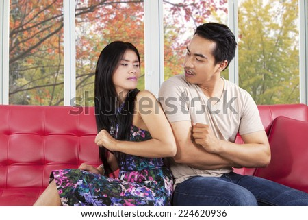 Portrait of couple quarreling at home while sitting on sofa and looking with hate - stock photo