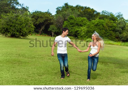 Portrait of couple running together in green park. - stock photo