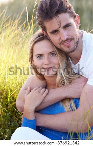 Portrait Of Couple Sitting In Sand Dunes - stock photo