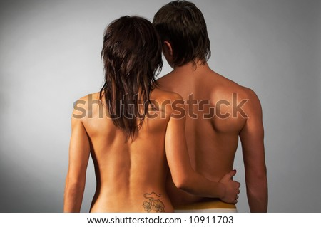 portrait of couple turned back on gray; tattoo on girl's back - stock photo